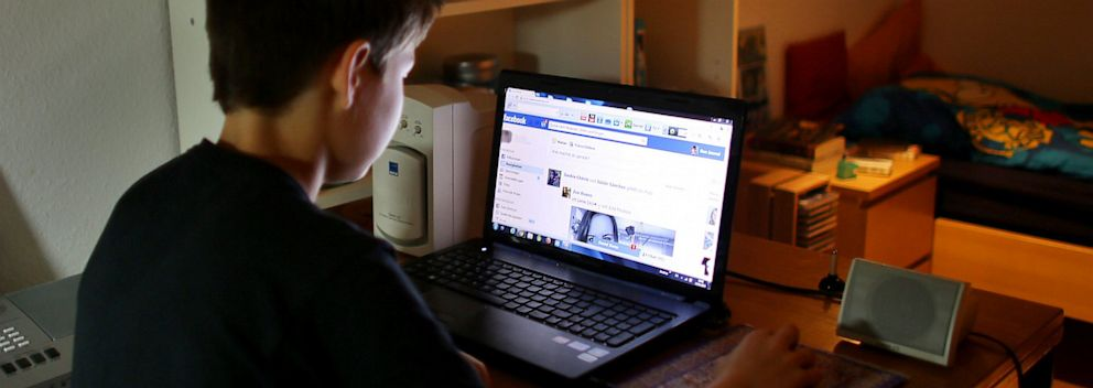 PHOTO: A teen looks at the Facebook website on his laptop, May 15, 2013.