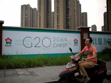 PHOTO: A man rides an electronic bike past a billboard for the upcoming G20 summit in Hangzhou, Zhejiang province, China, July 29, 2016.