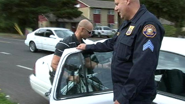 PHOTO: Portland police Stg. Dan Slauson and officer Jason Lobaugh put a stolen bike recovered from a Craigslist sting in the back of a squad car.