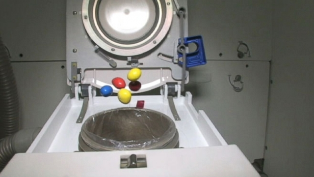 Astronaut Cady Coleman tosses M&Ms into the space station toilet to show how waste is dealt with.