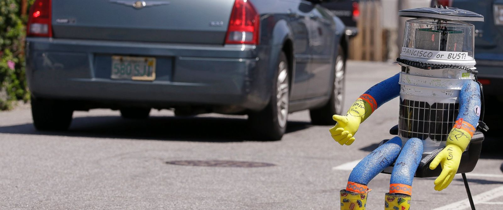 PHOTO: In this July 17, 2015, file photo, a car drives by HitchBOT, a hitchhiking robot in Marblehead, Mass.