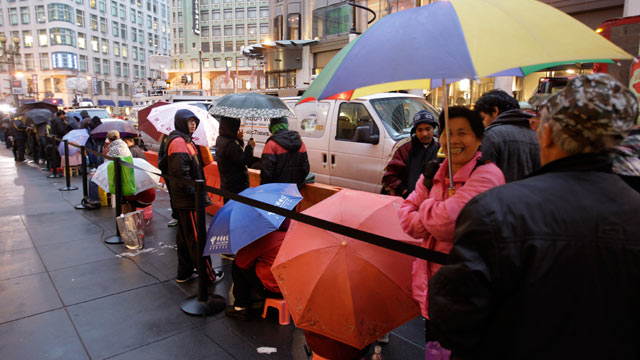 PHOTO: Apple customers take cover from the rain as they wait in line at an Apple store on the first day of the launch of the new iPad, in San Francisco, March 16, 2012.
