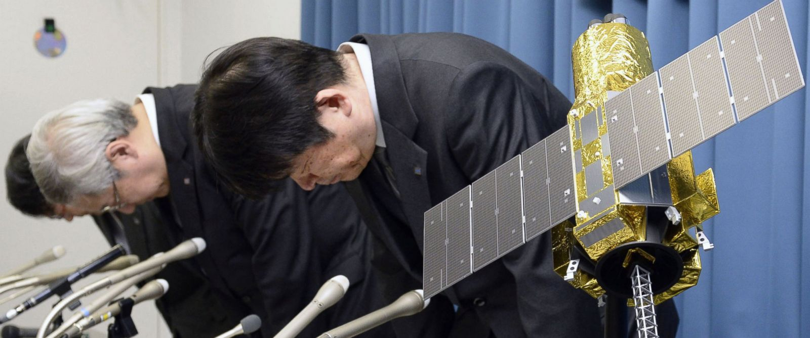 """PHOTO: Officials of the Japan Aerospace Exploration Agency bow beside the model of an X-ray astronomy satellite called """"Hitomi"""" in the agency in Tokyo, Japan, April 28, 2016."""