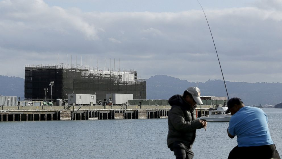 PHOTO: Two men fish in the water in front of a barge on Treasure Island in San Francisco, Oct. 29, 2013.