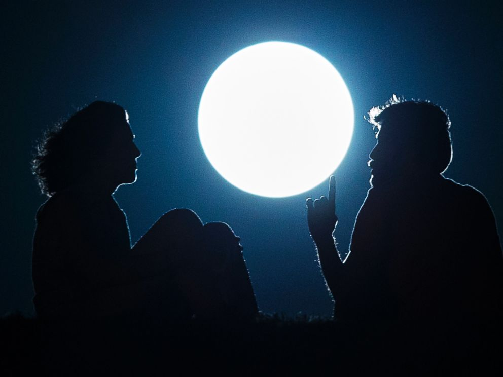 PHOTO: A couple talk as they sit against the perigee moon, also known as a supermoon, in Madrid, Aug. 10, 2014.