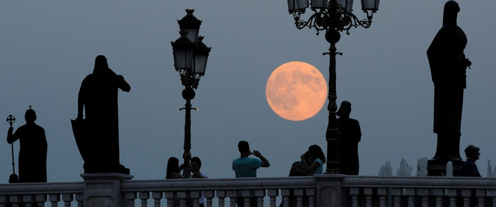 PHOTO: People take photos as a perigee moon also known as a supermoon rises above a bridge over Vardar River in Skopje, Macedonia, Aug. 10, 2014.