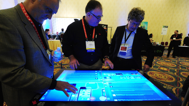 PHOTO: People sample a 3M Touch Systems 46-inch PCT-display demonstrating the scalability of projective capacitive technology at CES Unveiled, ahead of the opening of the annual Consumer Electronics Show, Jan. 8, 2012 in Las Vegas, Nevada.