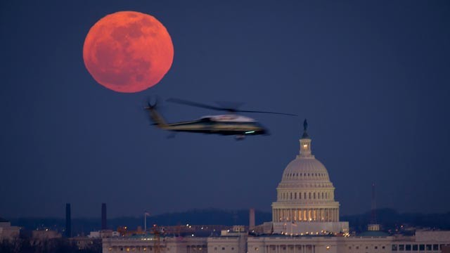 PHOTO: A full moon lights the sky as a United States Marine Corps helicopter flies past the U.S. Capitol on February 7, 2012, in Washington, DC.