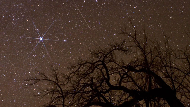 PHOTO: A Geminid meteor, top center, passes the bright star Sirius in the night sky.