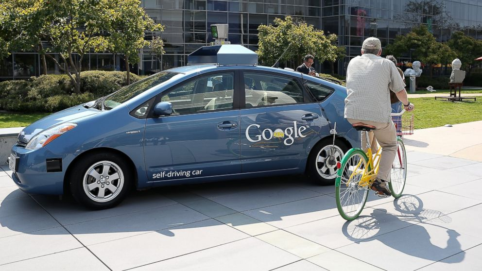 PHOTO: A bicyclist rides by a Google self-driving car at the Google headquarters, Sept. 25, 2012 in Mountain View, California.