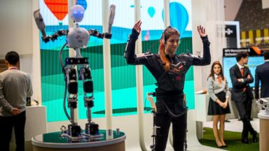 PHOTO: A hostess performs with robot under control by 5G Technology at the SK Telekom pavilion during the Mobile World Congress 2015, March 3, 2015 in Barcelona, Spain.