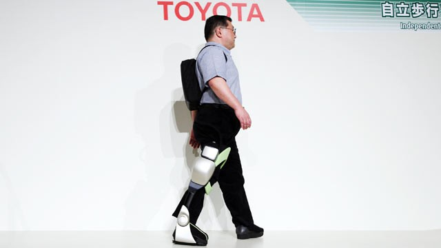PHOTO: Eiichi Saito, a professor at Fujita Health University, demonstrates an Independent Walk Assist robot at a Toyota Motor Corp.