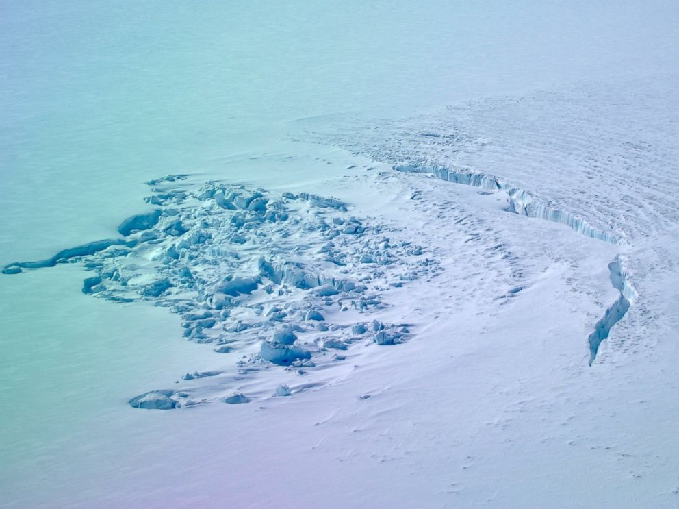 PHOTO: In April 2014, researchers flew over a site in southwest Greenland to find that a sub-glacial lake had drained away. This photo shows the crater left behind, as well as a deep crack in the ice.