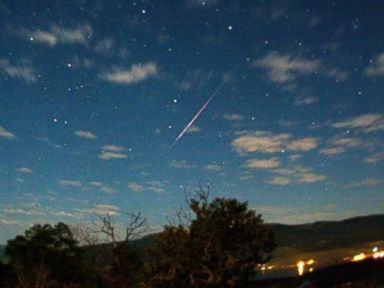 PHOTO: A perseid meteor streaks across a star-encrusted and cloud-scattered sky.
