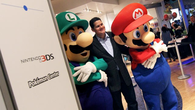 PHOTO:&nbsp;Nintendo of America President Reggie Fils-Aime poses with Mario and Luigi on Wii U launch night.