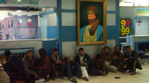 PHOTO: A crowd sits under a photo of Col. Moammar Gadhafi in the airport in Tripoli.