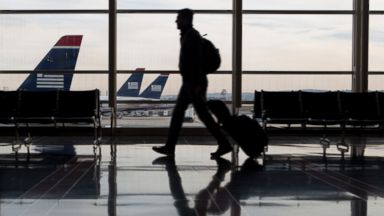 PHOTO: A traveler is seen walking past US Airways planes parked on the tarmac at Ronald Reagan National Airport in Washington, Nov. 15, 2013.