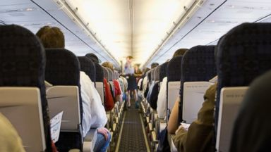 PHOTO: Passengers sit in a full airplane.