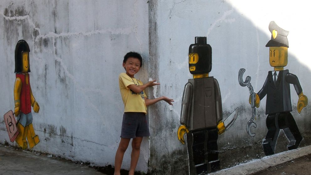 PHOTO: Lithuanian artist Ernest Zacharevics controversial mural depicts a Lego woman with a Chanel bag , a Lego robber with a knife on a wall in Johor Bahru, Malaysia.