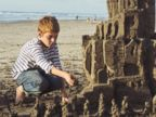 PHOTO: A boy puts builds a sandcastle on the beach in San Diego.
