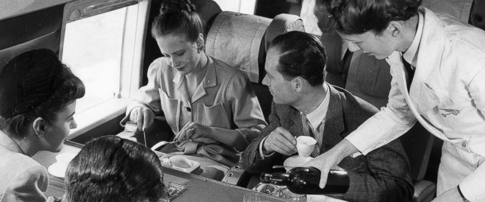 PHOTO: A stewardess serving drinks whilst passengers have lunch aboard a BEA Vickers Viking passenger plane, circa 1958.