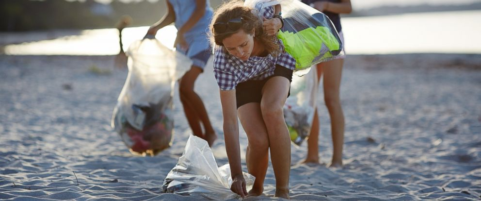 PHOTO: People pickup trash on a beach.