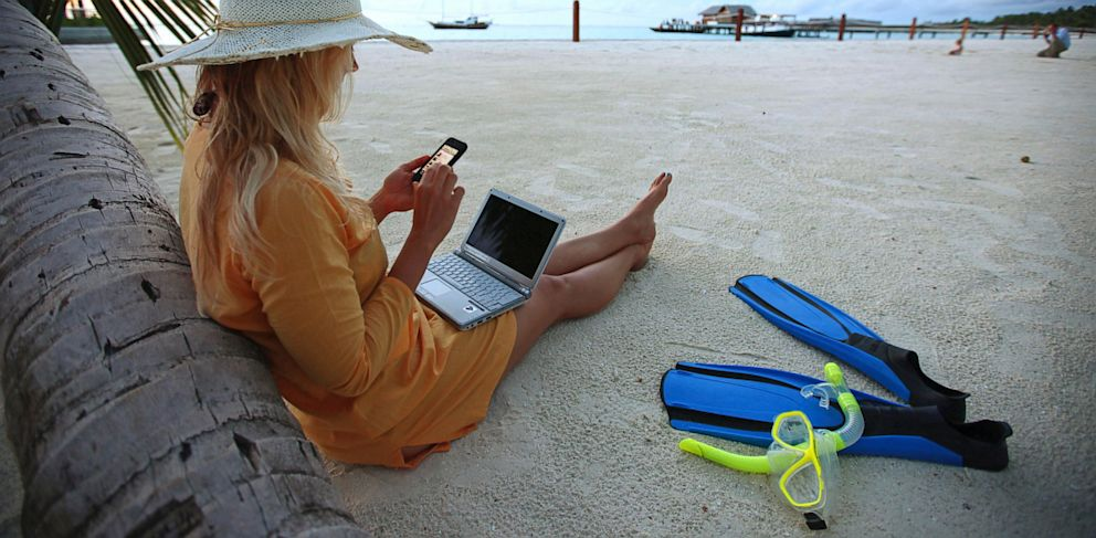 PHOTO: A woman sits on Villingili beach, working with a notebook and mobile phone.