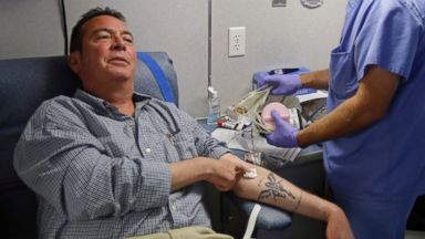 PHOTO: Technician Greg Snyder finishes up a blood draw from Chris Page after he donated blood in an Indiana Blood Center Bloodmobile in Indianapolis, Aug. 20, 2013.