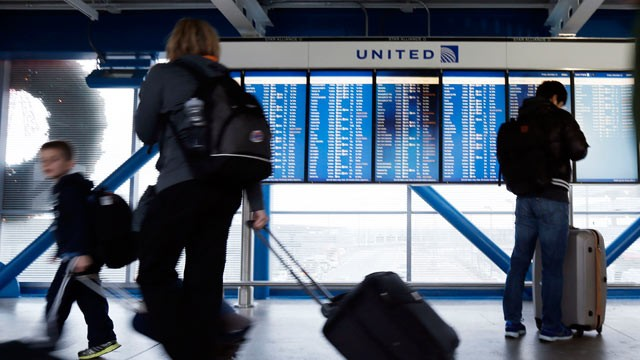PHOTO: In this Dec. 21, 2012, file photo, travelers walk in front of an United Airline flight information screen at O'Hare airport in Chicago.