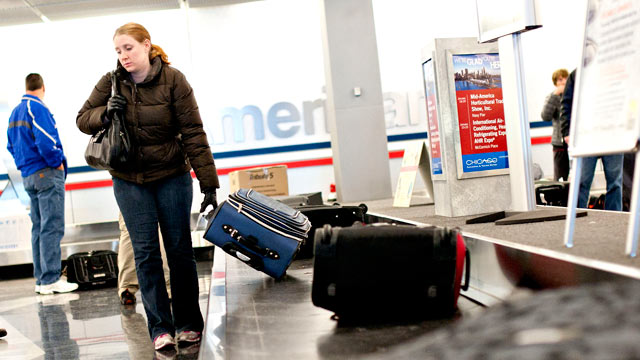 PHOTO: Passengers pick up their bags off the baggage claim belt at OHare International Airport in Chicago, Ill., Jan. 19, 2012.