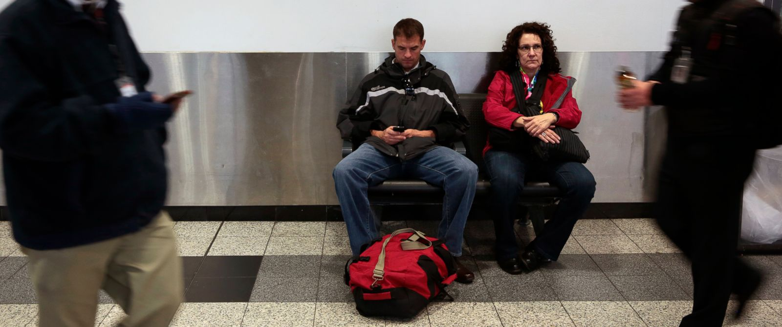 PHOTO: Two travelers wait in the ticketing area of B terminal at La Guardia Airport in New York, Jan. 17, 2014.