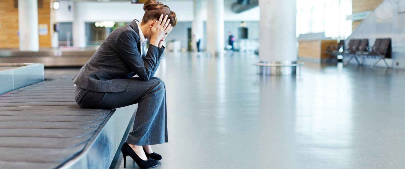 PHOTO: A woman holds her head while sitting on a baggage claim carousel in an undated stock photo.