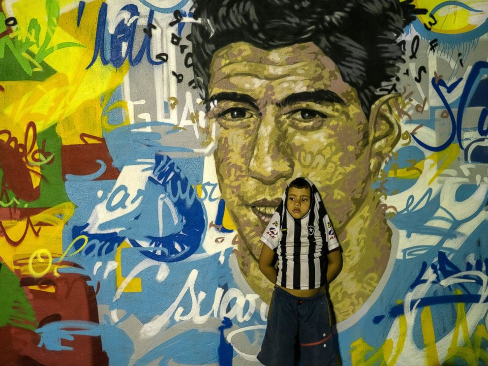 PHOTO: A boy leans on a mural with the portraits of famous football players at Tavares Bastos favela in Rio de Janeiro, Brazil, on May 21, 2014.