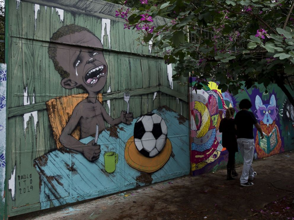 PHOTO: People walk past a graffiti painted by Brazilian street artist Paulo Ito on the entrance of a public schoolhouse in Sao Paulo, Brazil on May 23, 2014.