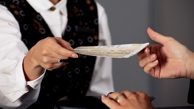 PHOTO: An airplane agent handing an airplane ticket to a passenger in this undated file photo.