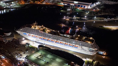 Crippled cruise ship, Carnival Triumph, moves into port guided by tug boats on Feb. 14, 2013 in Mobile, Ala.