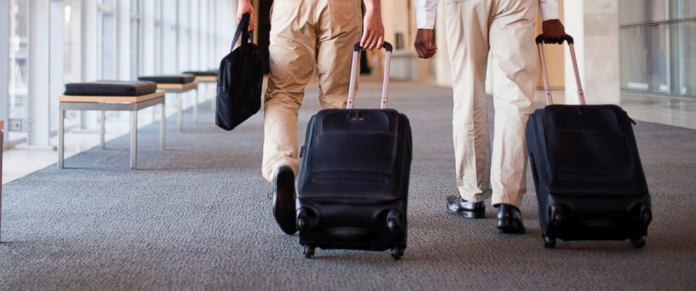PHOTO: Businessmen roll luggage in hallway in this undated stock image.