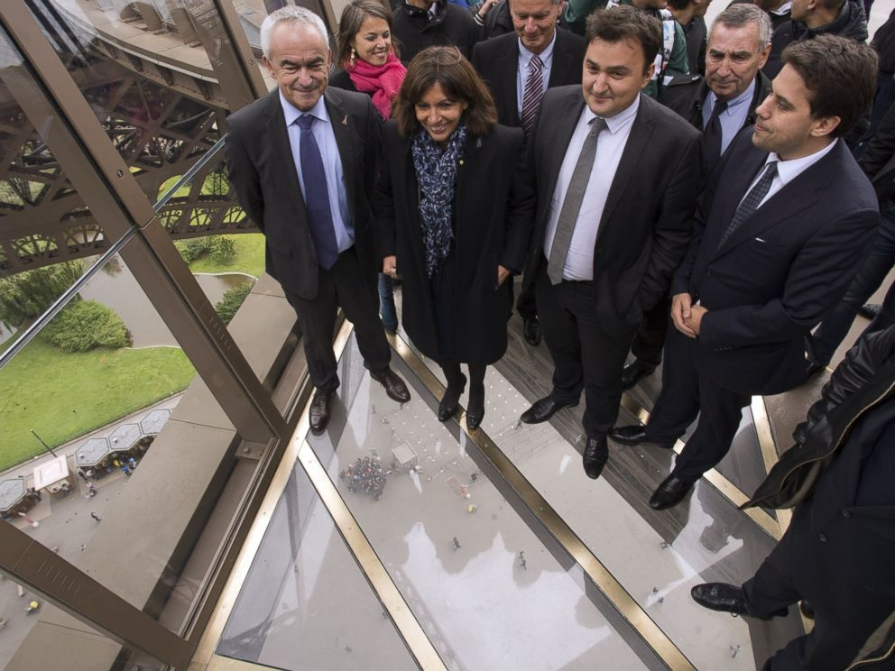 PHOTO: Paris mayor Anne Hidalgo (C) walks on the new glass floor at the Eiffel Tower during its inauguration in Paris on Oct. 6, 2014.
