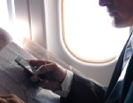 PHOTO: Man using smartphone on airliner