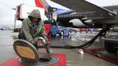 PHOTO: Swissport employee Christopher Gonzalez disconnects a fuel line from an underground fuel tank after he refueled a Southwest Airlines plane at the Oakland International Airport in Oakland, Calif., Feb. 24, 2011.