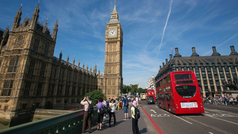 PHOTO: Tourists stand on Westminster Bridge as they take photographs of the Big Ben clock tower at the Houses of Parliament from Westminster Bridge in London, U.K., on July 15, 2013.