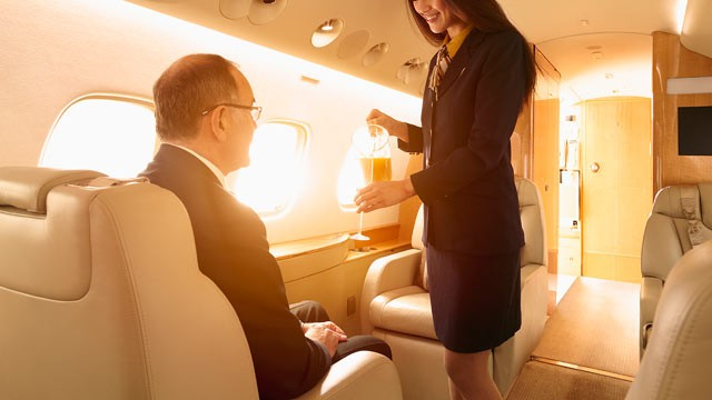 PHOTO: A flight attendant brings a passenger a drink on a private flight.