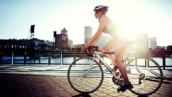 PHOTO: A woman commutes to work by bike, the evening sun setting over downtown Portland, Oregon and the Willamette River.