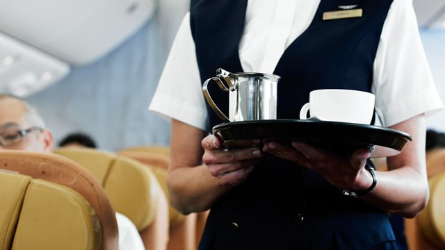 PHOTO: An airline steward brings coffee to a passenger.
