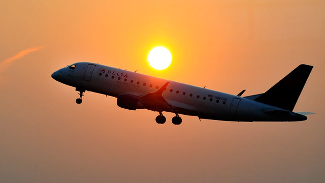 PHOTO: A Delta airlines aircraft takes off from the Ronald Reagan National airport as the sun rises in Washington,