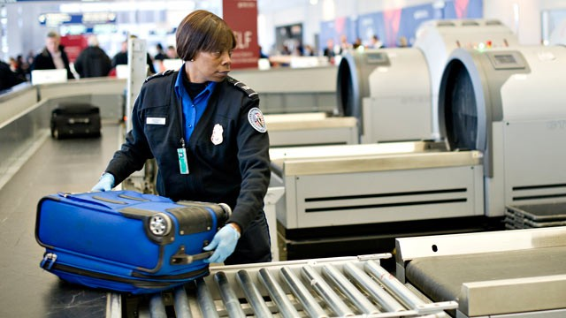 PHOTO: A Transportation Security Administration employee moves a checked piece of passenger luggage toward a scanning machine at a security check point at O'Hare International Airport in Chicago, Ill.