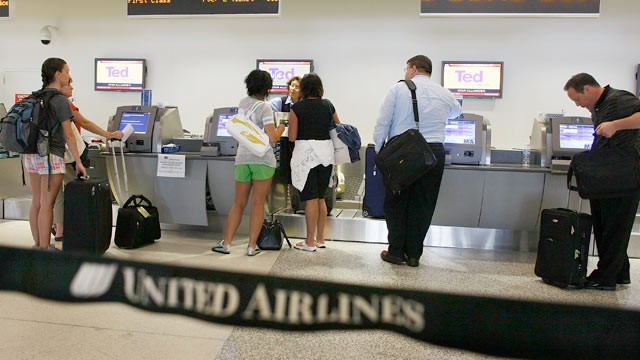 PHOTO: Passengers check in with their baggage at the United Airlines counter at the Miami International Airport, June 2008 in Miami, Fla.