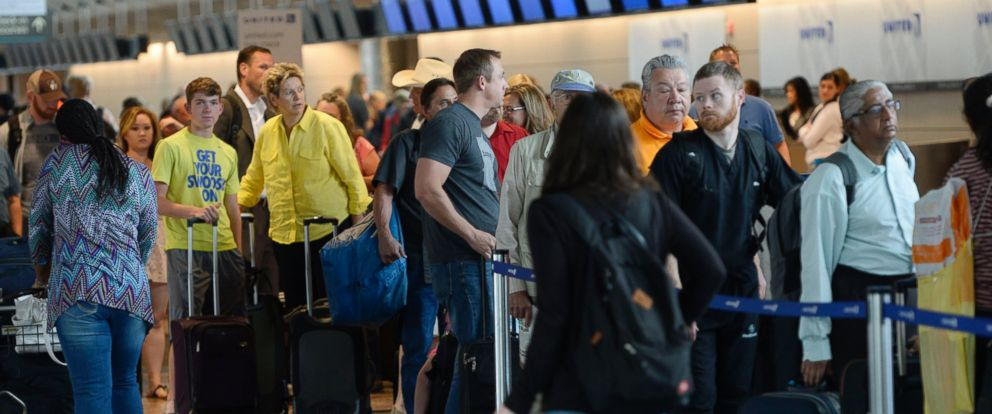 PHOTO: Long lines of passengers wait at the United Airlines ticket counter at Denver International Airport, July 08, 2015.