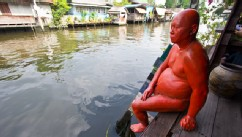 PHOTO: A life-size statue of a pot-bellied man dipping his toe into the water, at the Artist's Village in Klong Bang Luong.