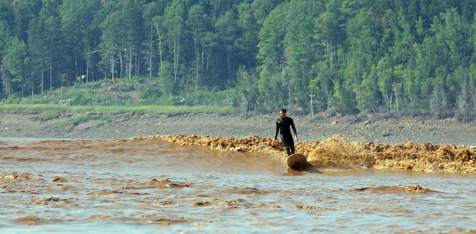 PHOTO: Colin Whitbread surfs a tidal bore on the Petitcodiac River in Moncton, New Brunswick.